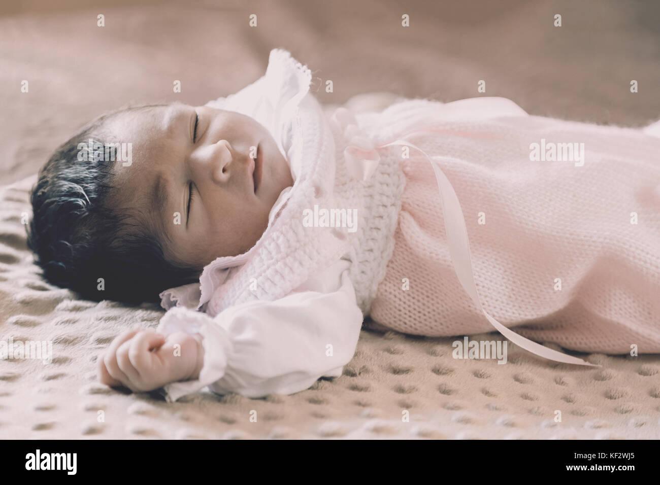Cute zwei Wochen alte Neugeborene Mädchen mit rosa stricken Kleidung, friedlich im Bett/neugeborenes Mädchen Stockbild