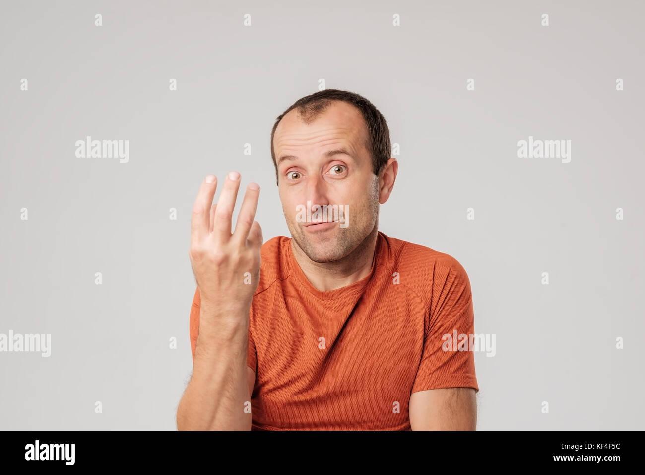 Ein erwachsener spanischer Mann in einem orange T-Shirt zeigt drei fongers in Zweifel. Er schaut in die Kamera in Stockbild