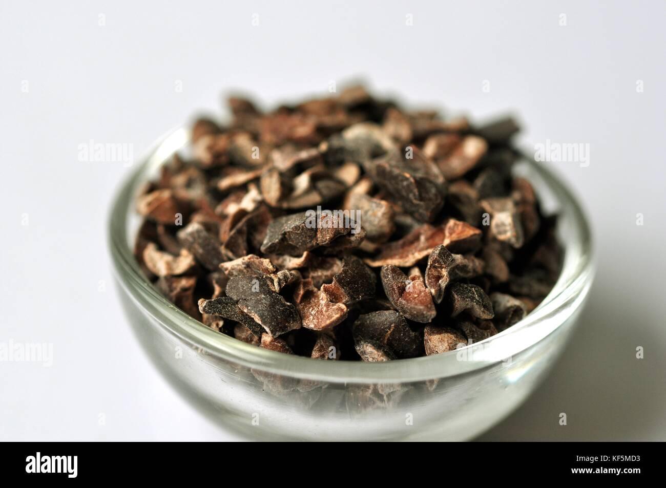 Rohe cacao Bohne (Theobroma cacao) Federn in eine Glasschüssel, isoliert auf Weiss. Nahrhafte Nahrungsergänzungsmittel Stockbild
