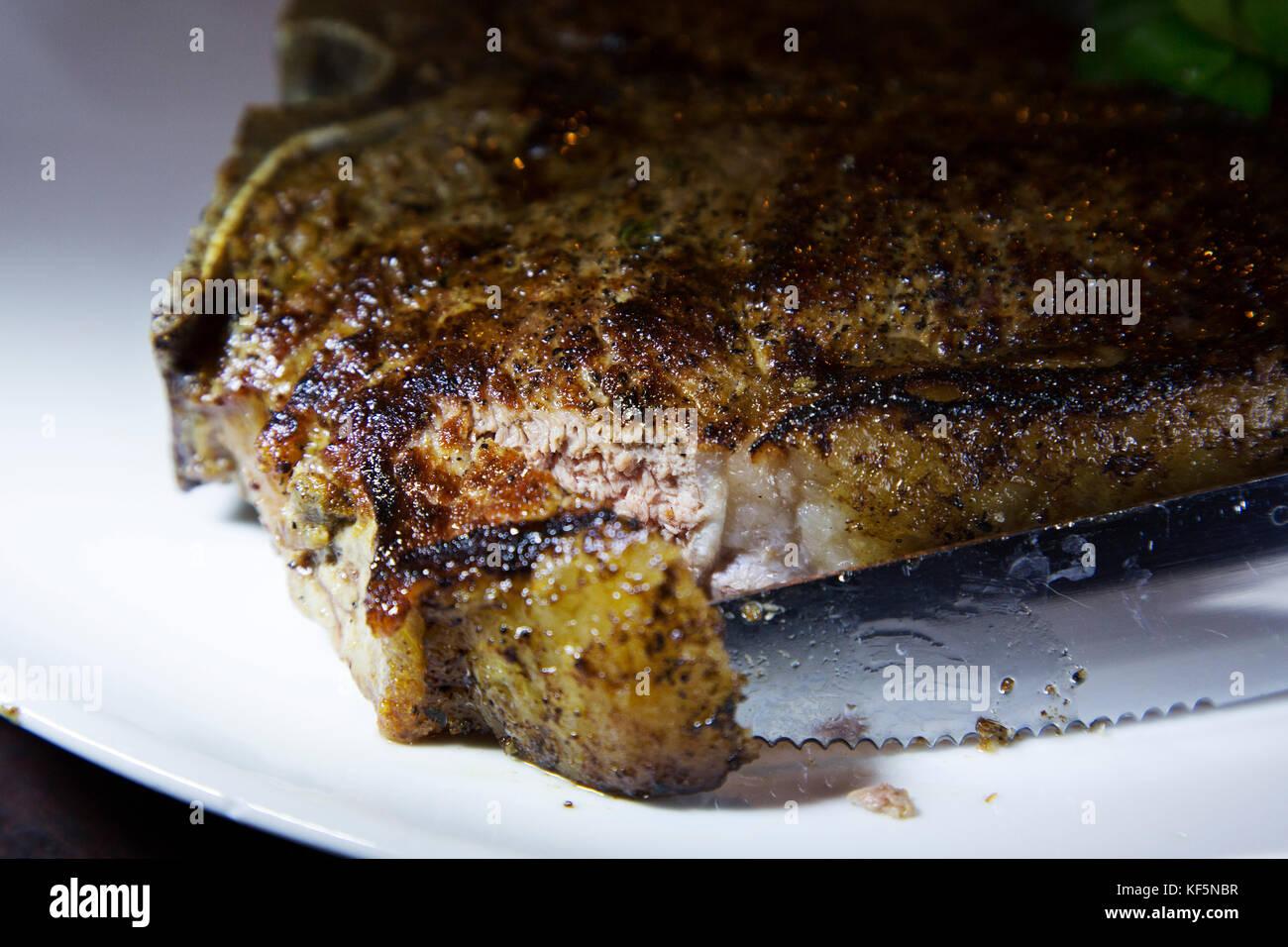 Ein Messer schneidet in ein T-Bone Steak Fleisch von einem britischen - angehobene Hereford Rind. Das Gericht mit Stockbild