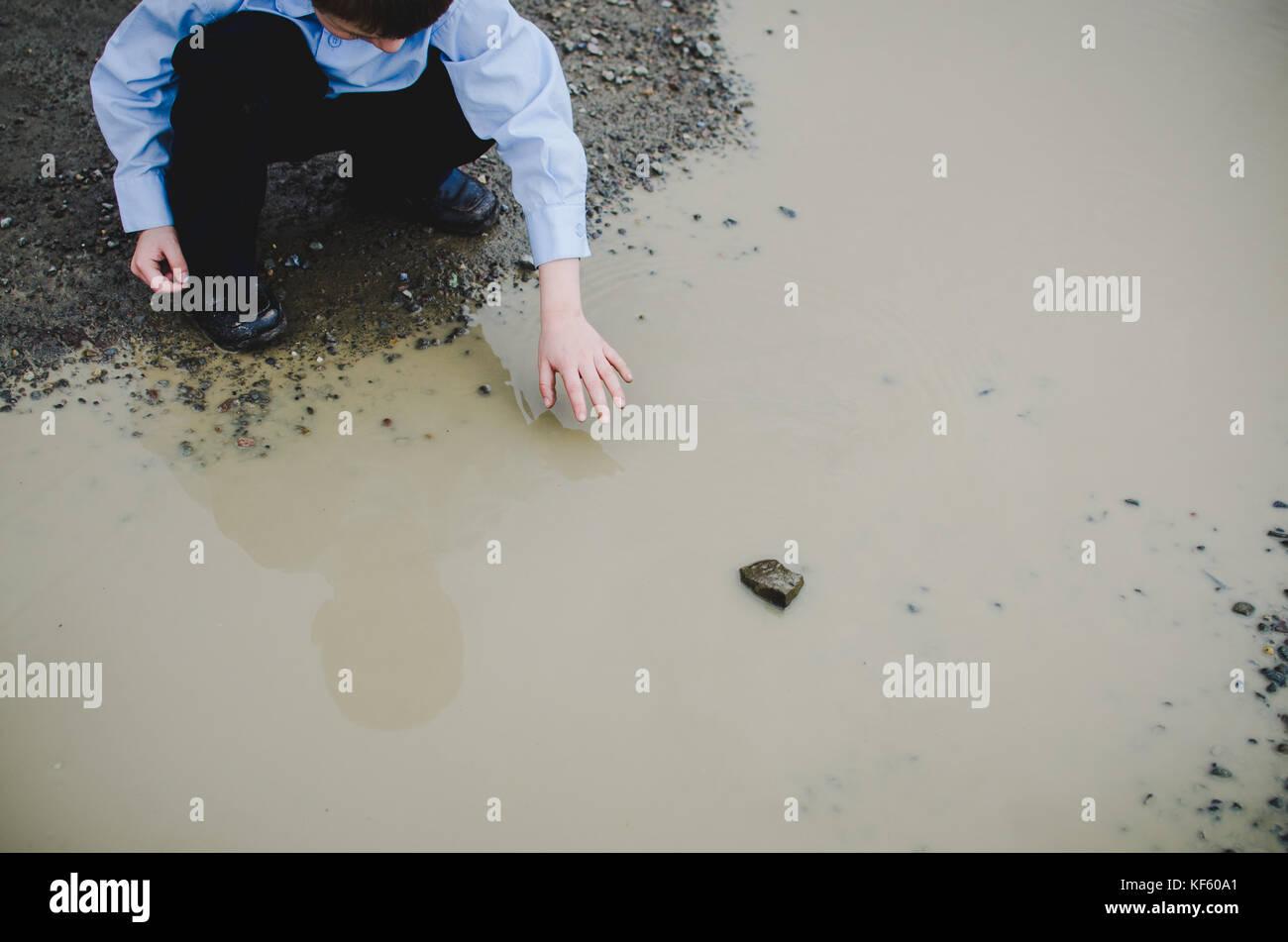 Ein Junge erreichen für ein Felsen in ein Schlammloch. Stockbild