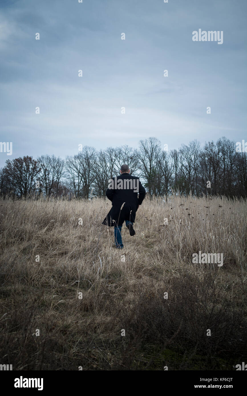 Rückansicht eines Mannes weg laufen in einem Feld Stockbild