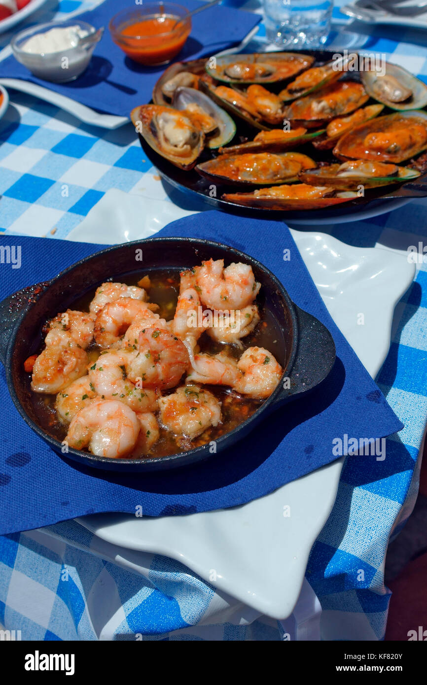 Gekochte Garnelen und Muscheln in heißen skillets auf einem blau karierte Tischdecke im Dorf El Cotillo, Fuerteventura Stockbild