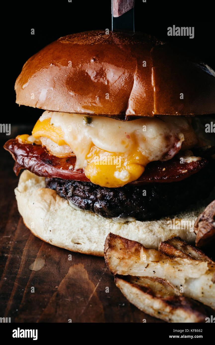 Giganic Burger mit Chorizo und ein Spiegelei mit Pommes frites auf dunklem Hintergrund im Landhausstil serviert. Stockbild