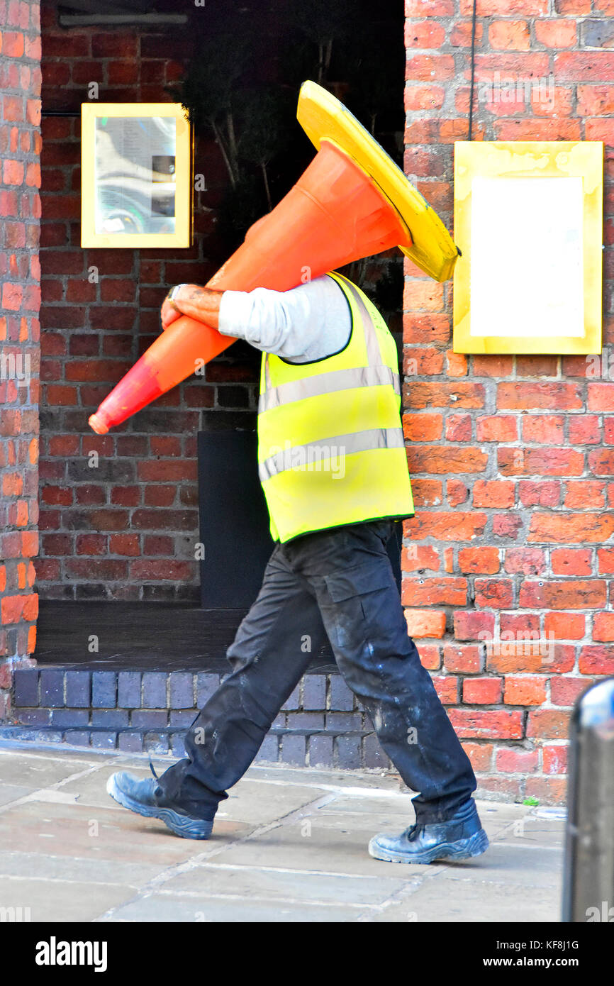 Mann bei der Arbeit entlang Plasterung in Liverpool tragen hohe Sichtbarkeit Jacke mit einem großen leitkegel Poller Stockfoto