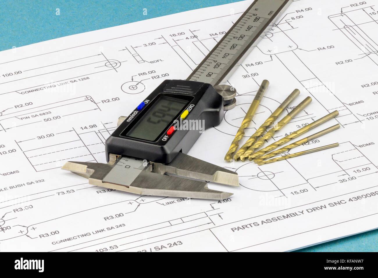 Messschieber und Bohrer auf technische Zeichnung Hintergrund platziert Stockbild