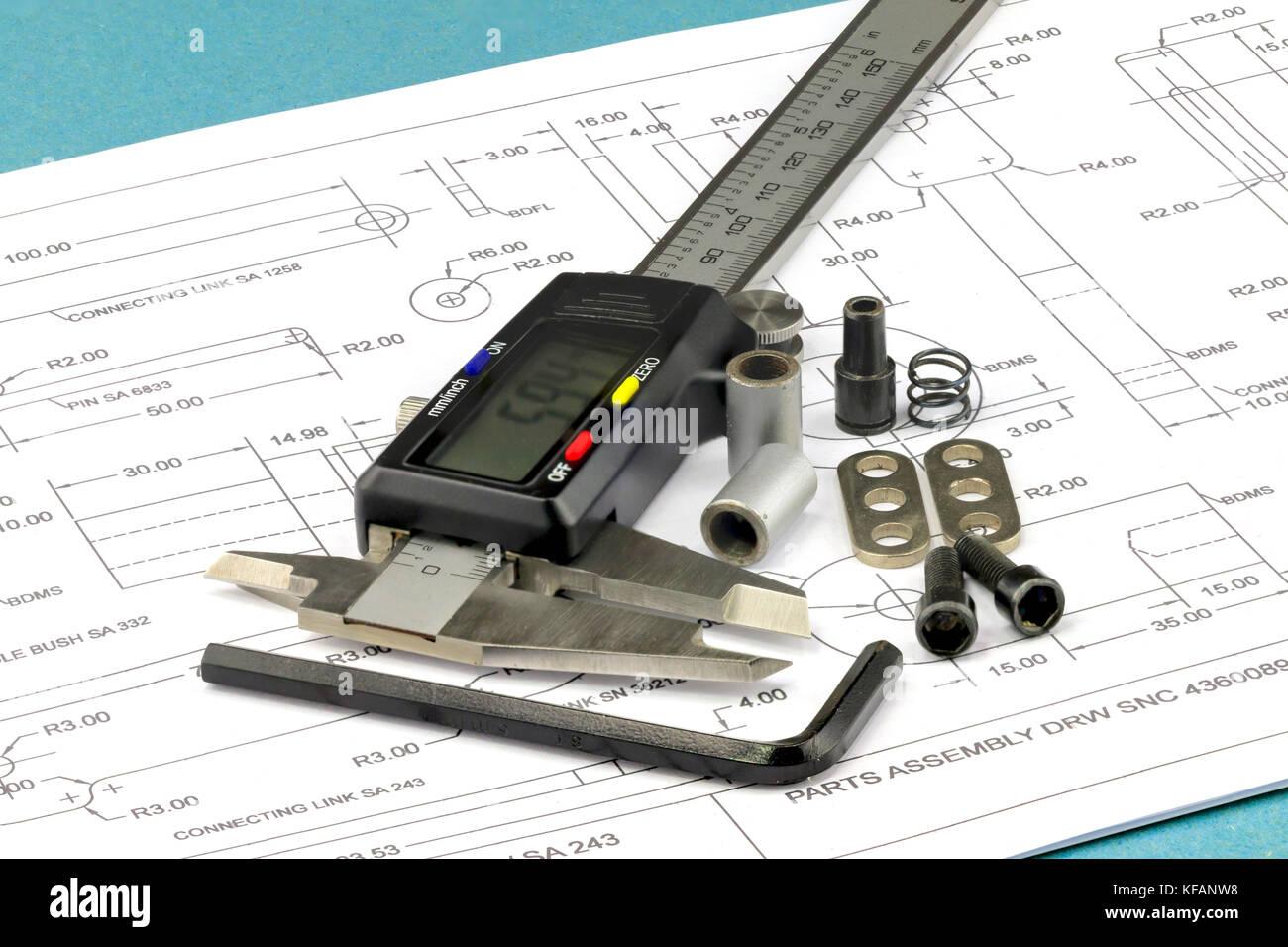 Messschieber, Metallteile und Inbusschlüssel auf einer technischen Zeichnung Hintergrund platziert Stockbild