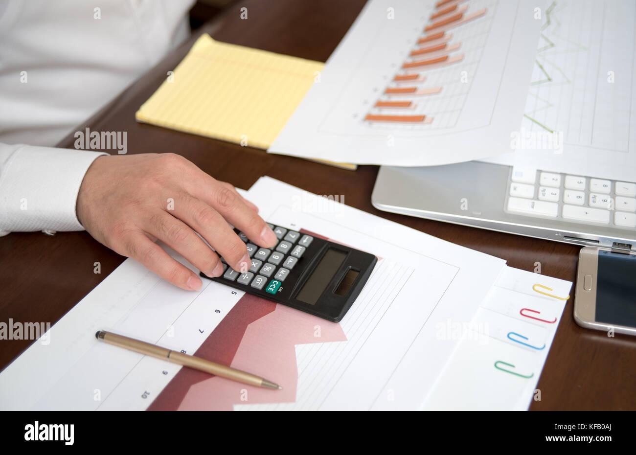 Der Mann ist die Überprüfung mit einem Taschenrechner.business Finanzen, Steuern, Buchhaltung, Statistik und analytische Stockfoto