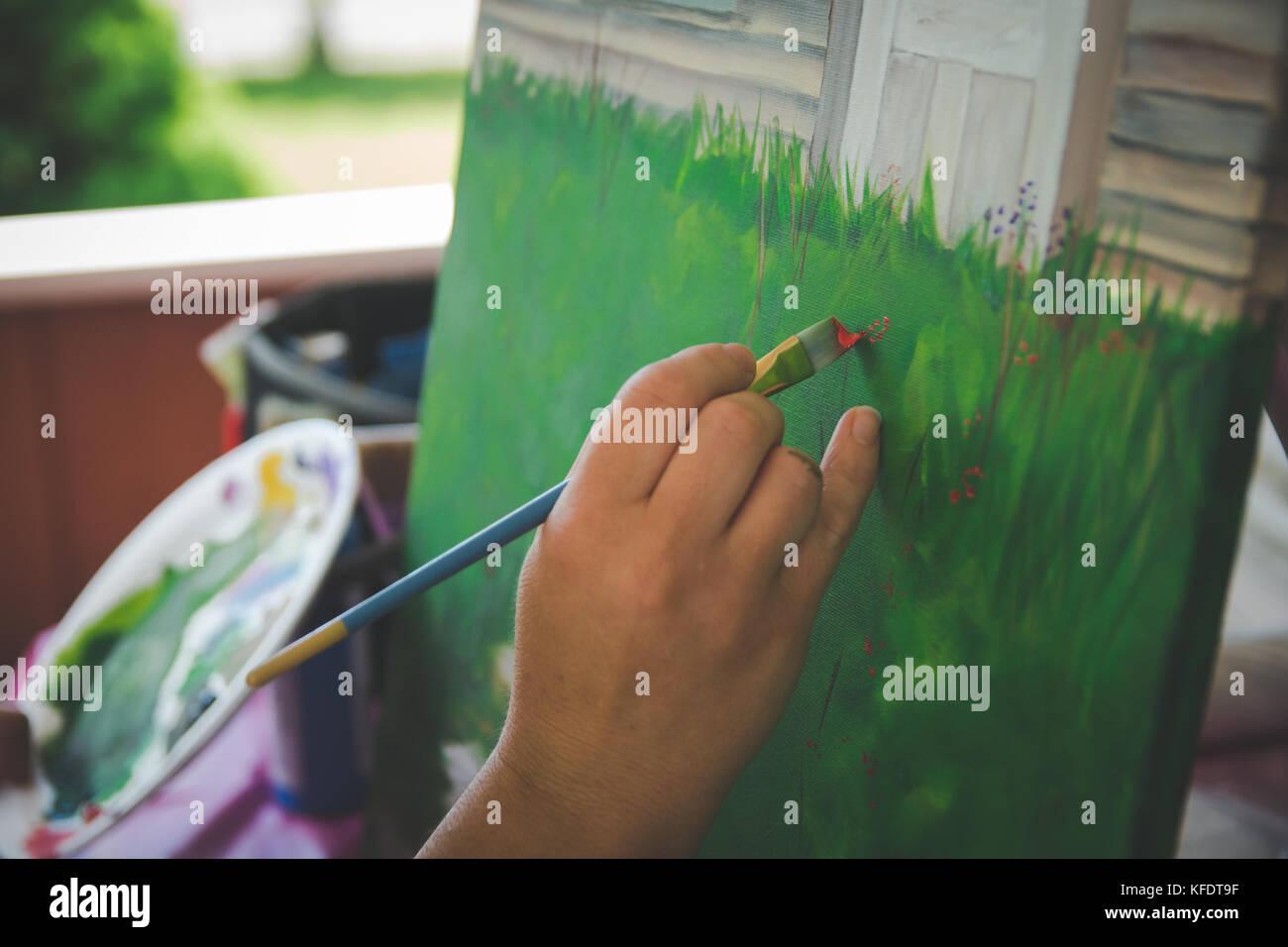 Artist holding Pinsel malen auf Leinwand Stockbild