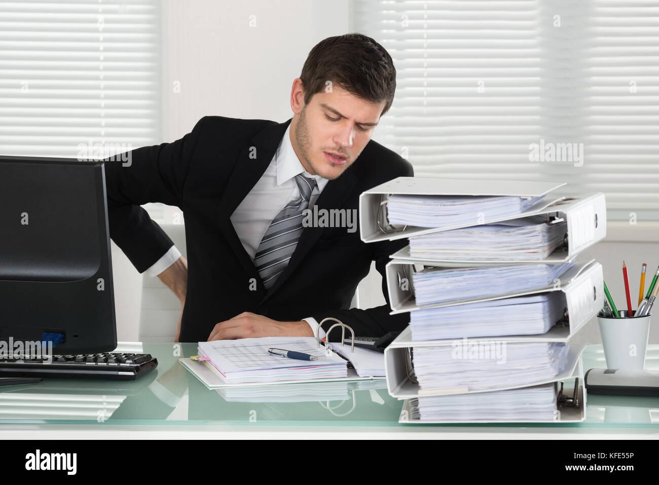 Unternehmer leiden unter Rückenschmerzen mit Rechnung auf Schreibtisch Stockbild