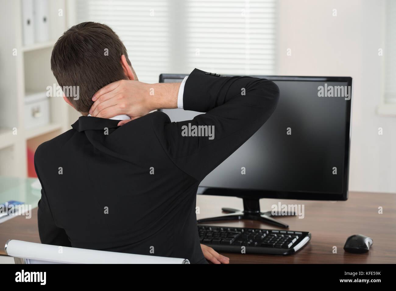 Unternehmer leiden unter Nackenschmerzen, während im Büro arbeiten Stockbild