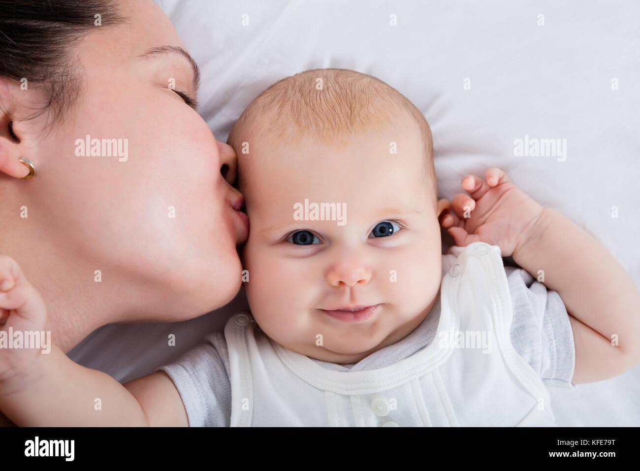 Nahaufnahme einer Mutter küssen ihr Baby auf der Stirn Stockbild
