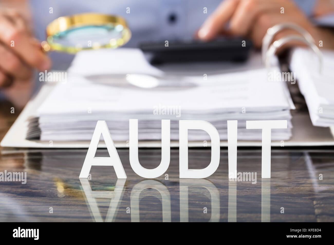 Nahaufnahme der Finanzdaten Analytiker mit Audit text auf Glas Schreibtisch im Büro Stockbild