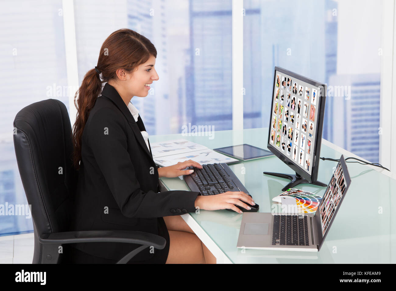 Junge geschäftsfrau an Farbmuster computer Schreibtisch im Büro suchen Stockbild