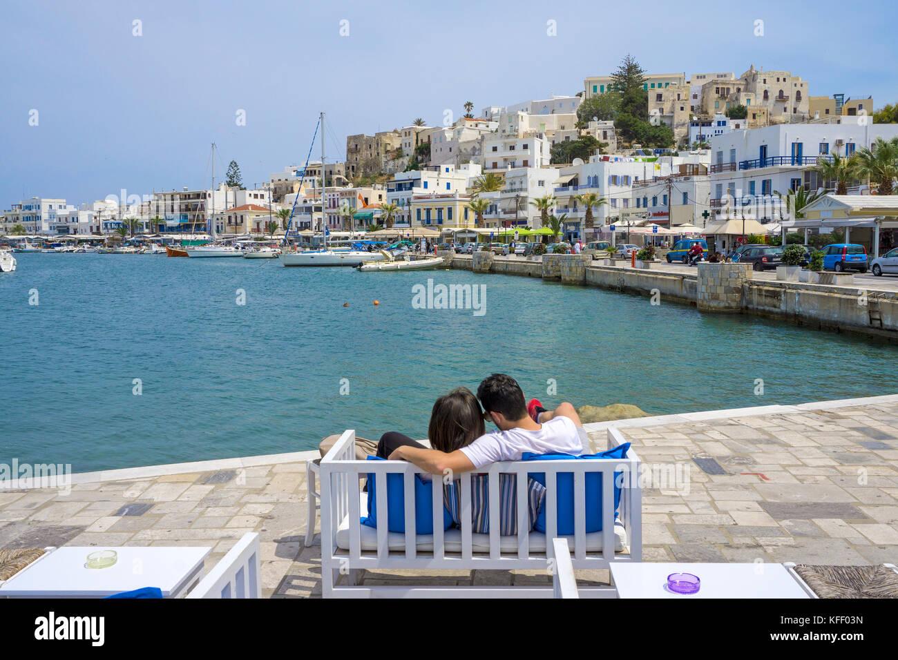 Junges Paar auf einer Bank präsentiert die Sicht auf den Hafen, Naxos, Insel Naxos, Kykladen, Ägäis, Stockbild