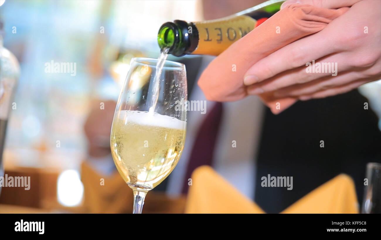 Der Champagner in ein Glas gießen. Barkeeper gießen Champagner in Glas, close-up. Champagner im Glas gießen Stockbild