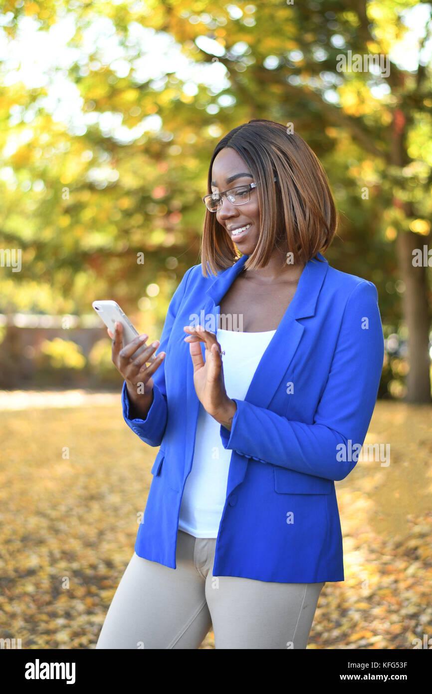 Eine starke junge schwarze Frauen mit einem Smartphone in einem Park im Herbst Stockfoto
