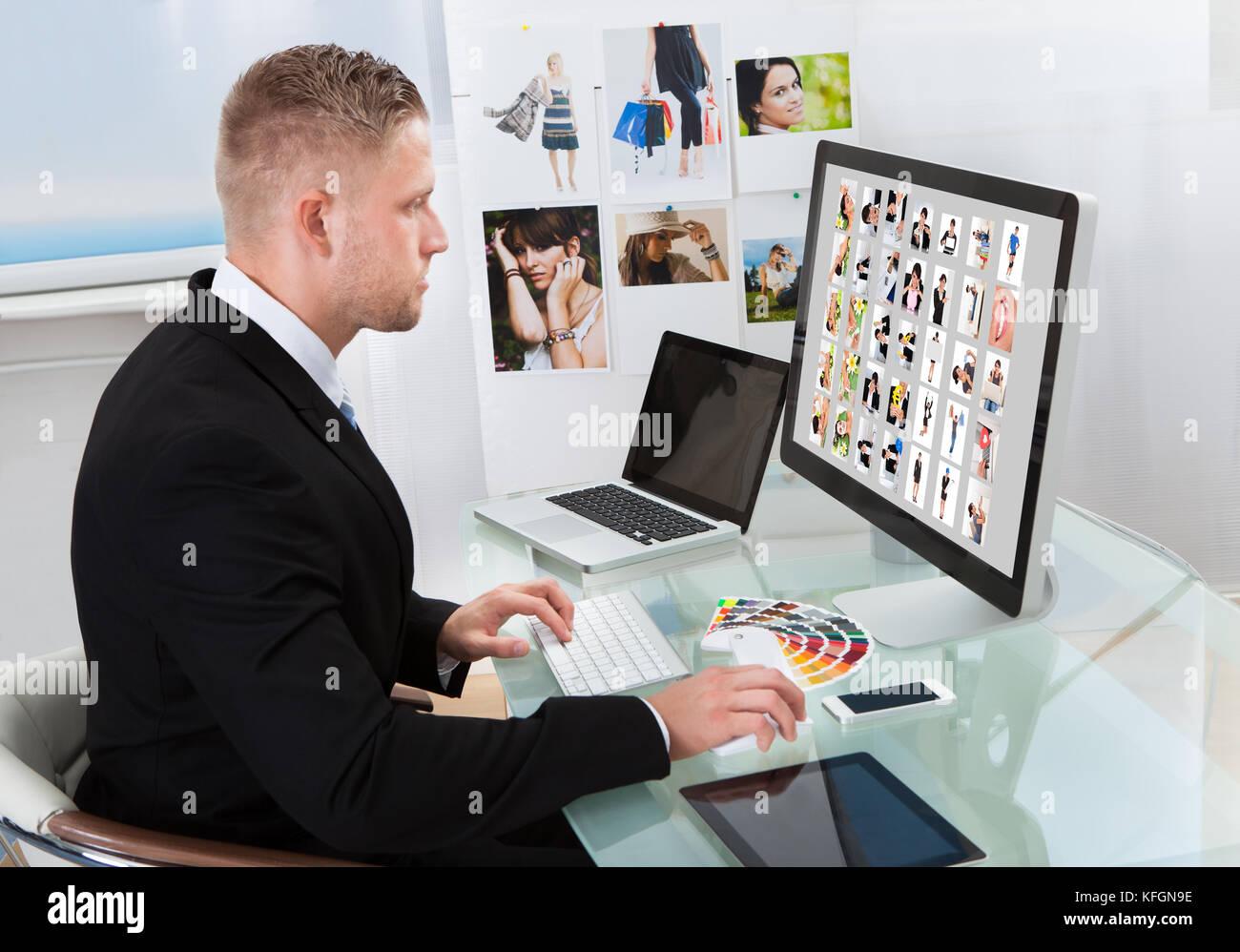 Geschäftsmann an seinem Schreibtisch vor einem großen Bildschirm Monitor bearbeiten Fotos sitzen Stockbild