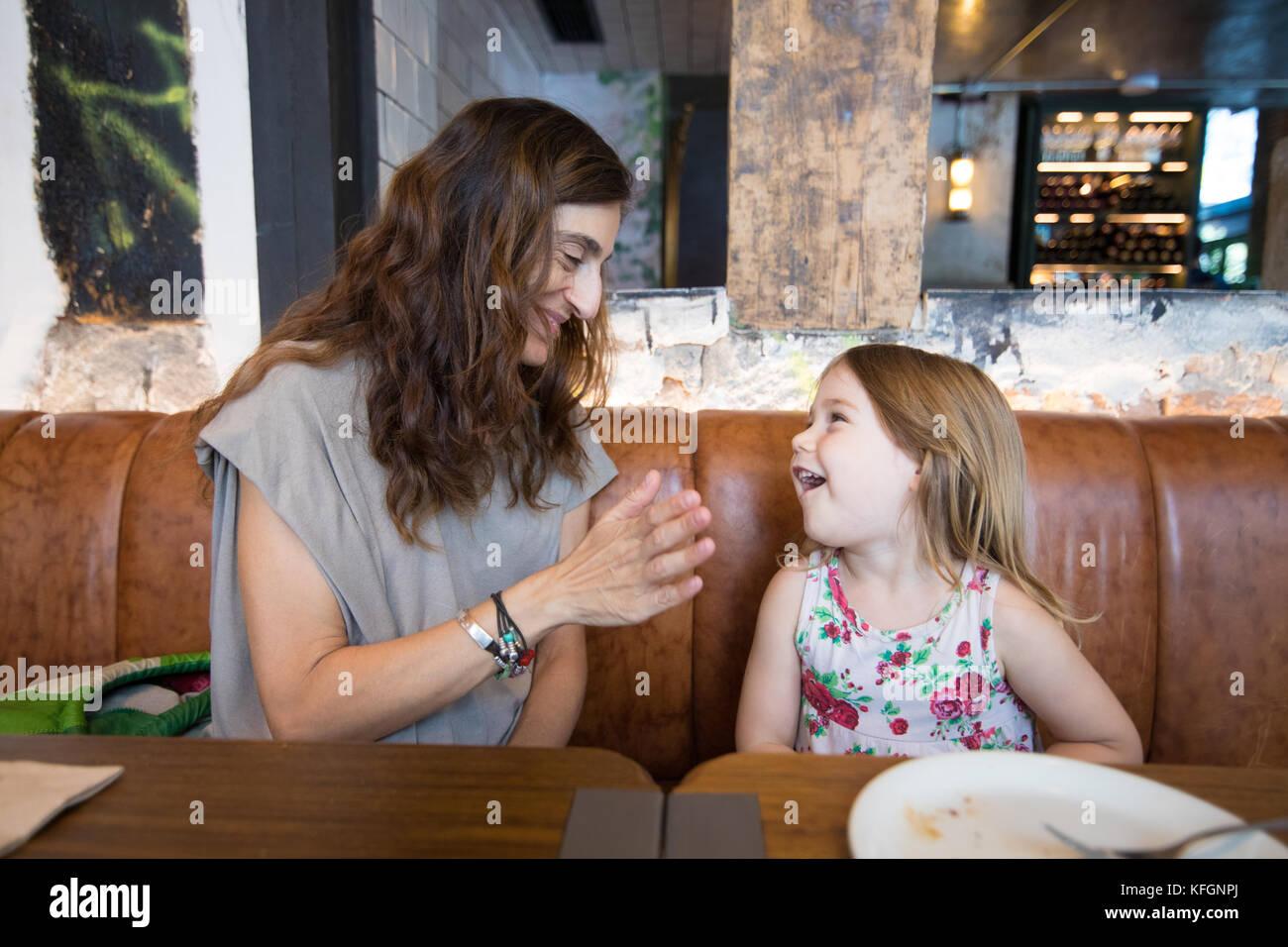 Vier Jahre alter Blondine glücklich lachen und sprechen mit Frau Mutter sitzen in braunem Leder Sofa im Restaurant Stockbild