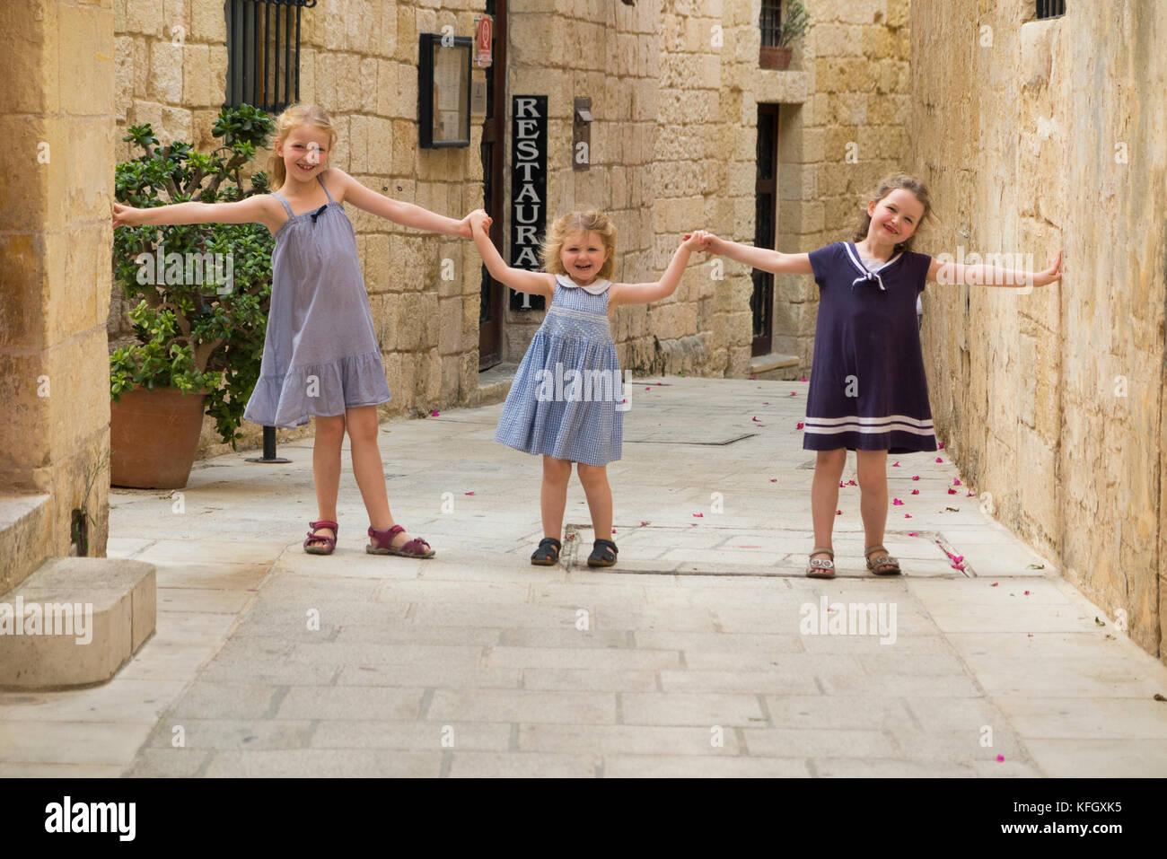 Drei junge Schwestern/Mädchen/Kinder/Kinder/Kind 7, 3, & 5 Jahre, für einen Familienurlaub, laufen Stockbild