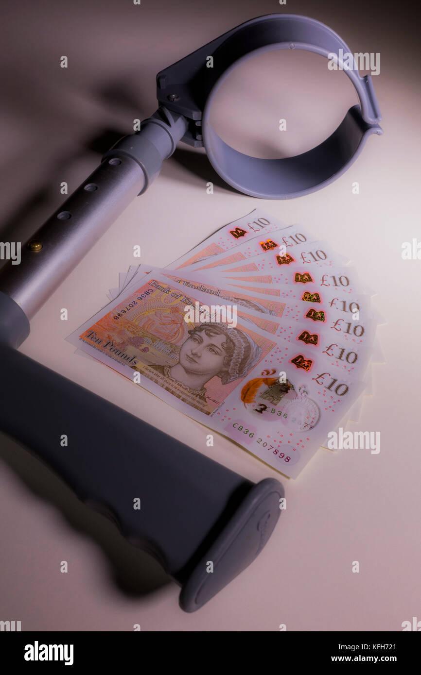 Krücke und neue Polymer Sterling £ 10 zehn Pfund Noten. Konzept der Zusammenhang zwischen Arbeitsunfähigkeit Stockbild