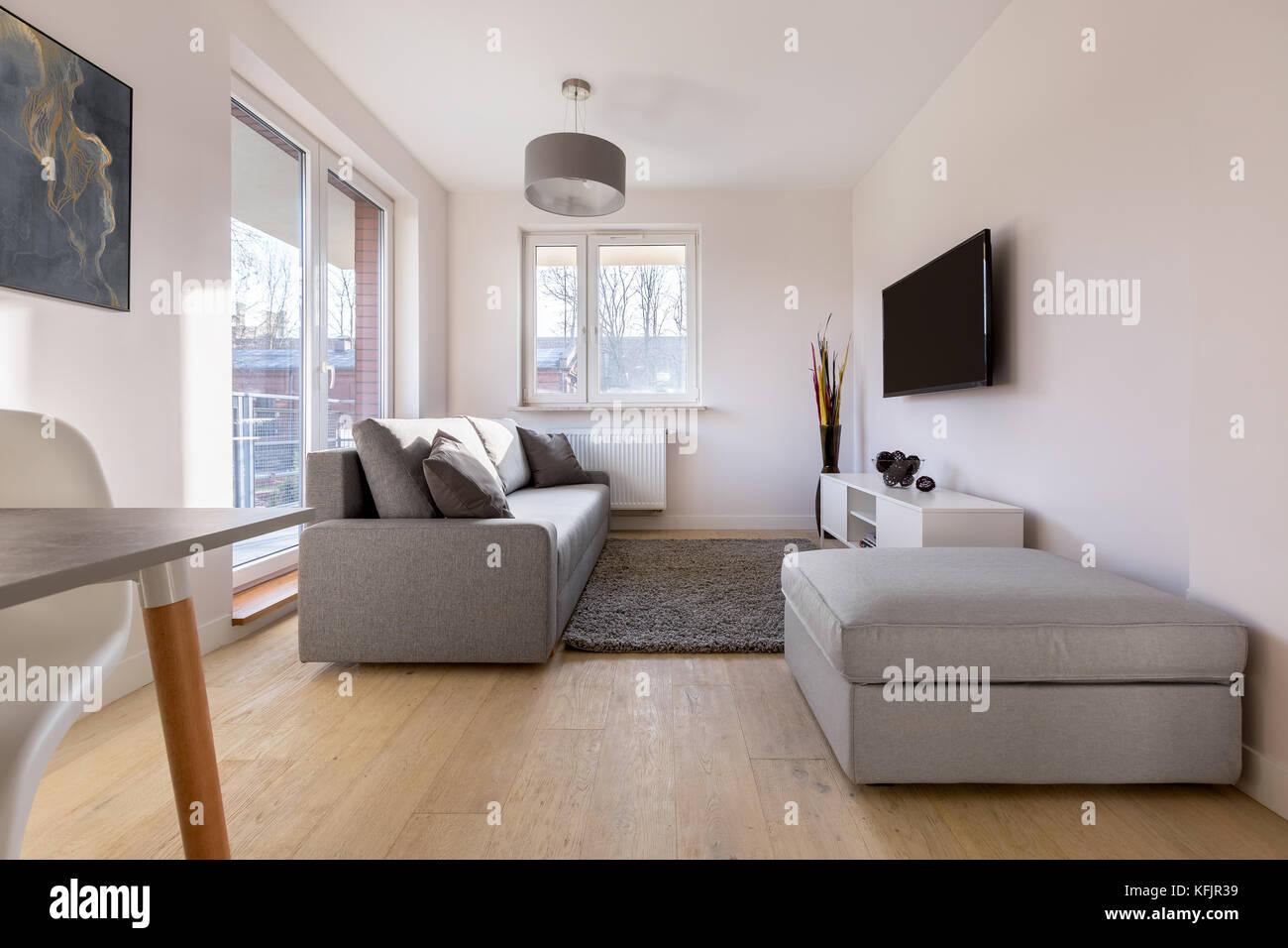 Gemutliche Wohnlandschaft Mit Schlafcouch Pouf Und Tv Stockfoto