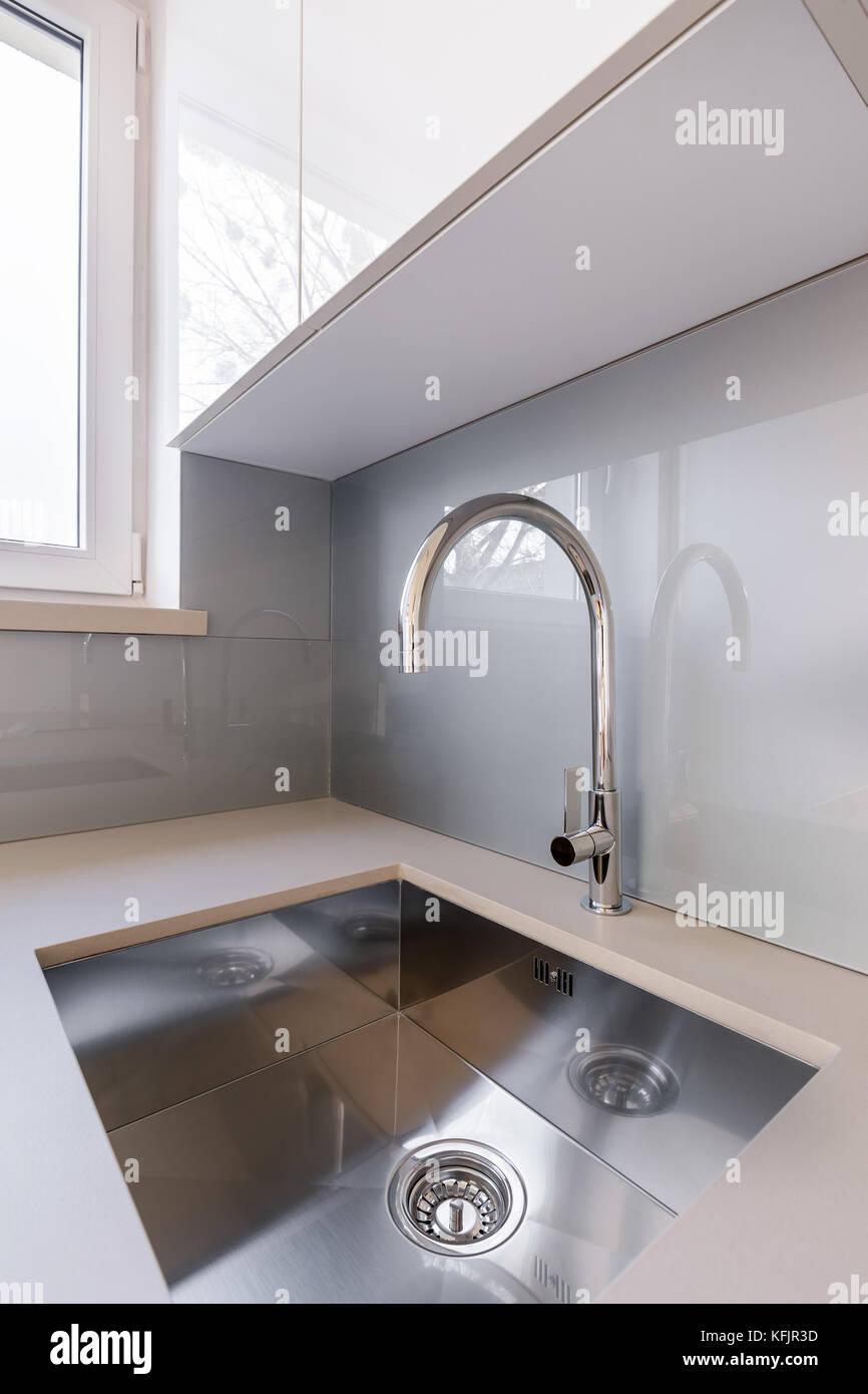 Weiße Küche mit eleganten Silber Waschbecken und Tippen ...