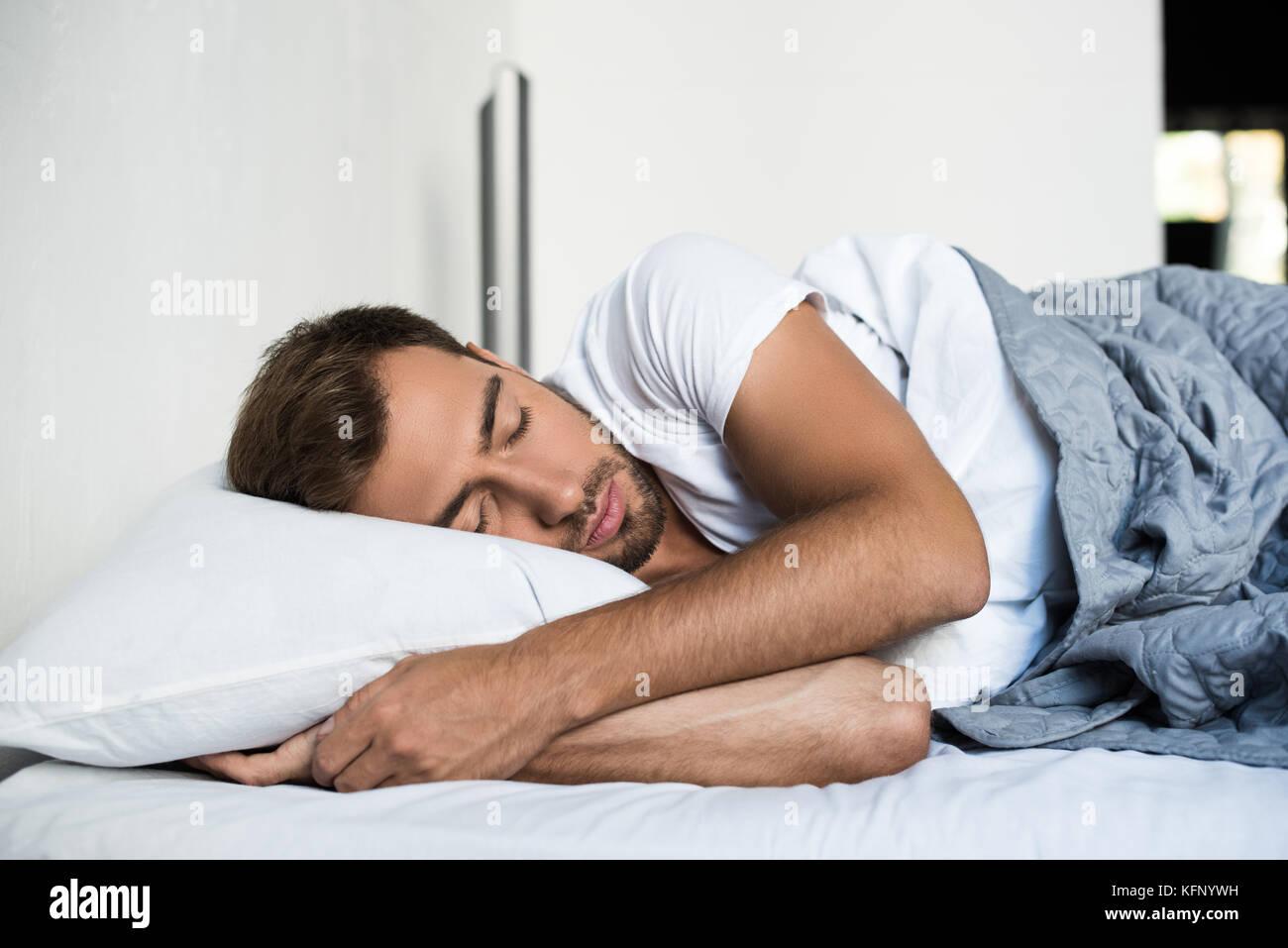 Mann schlafen im Bett Stockbild