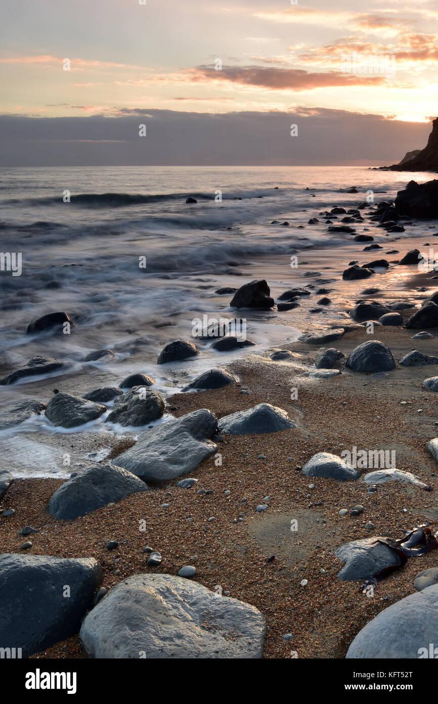 Eine schöne und atmosphärische Meereslandschaft mit nassen Felsen im Vordergrund und Sandstrand mit Wellen Stockbild