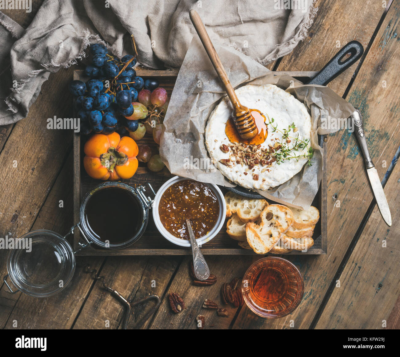 Camambert mit Honig, Nüsse, Kräuter, Obst und Wein Stockbild