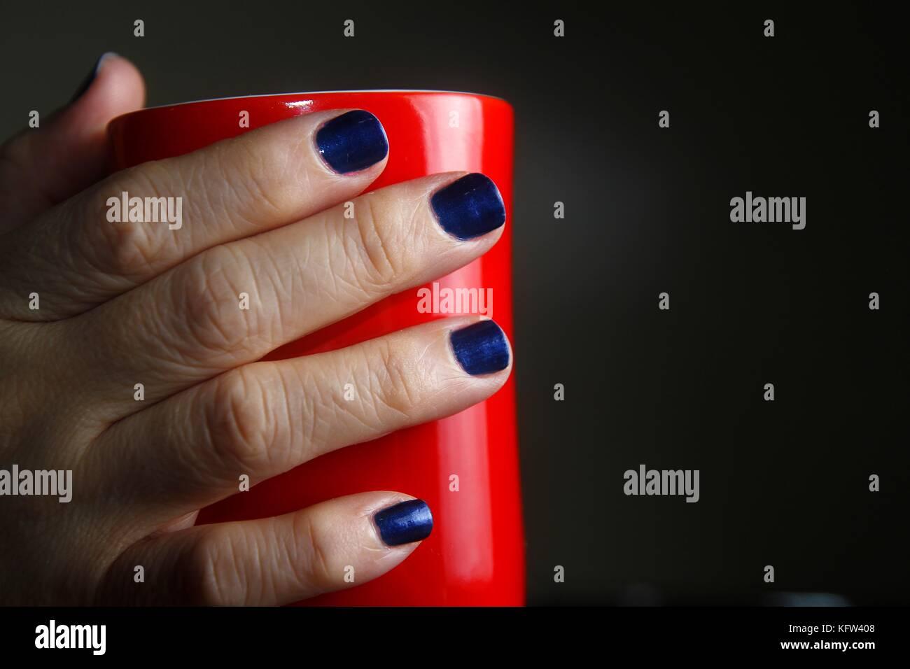 Foto von einem Paar Hände mit polierten Nägel rote Kaffeetasse ...
