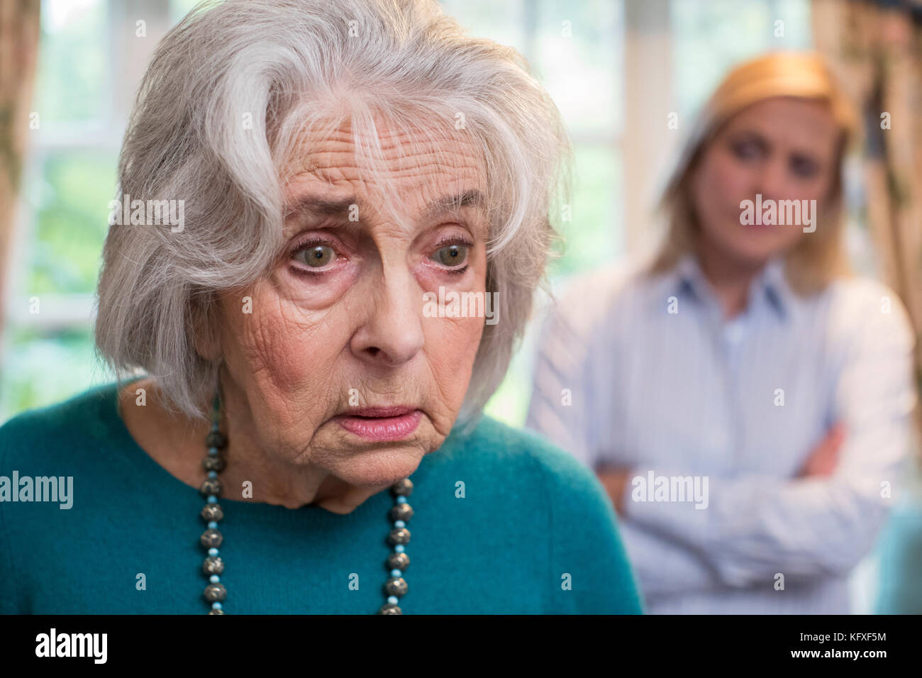 Verwirrte ältere Frau mit erwachsenen Tochter zu Hause Stockbild