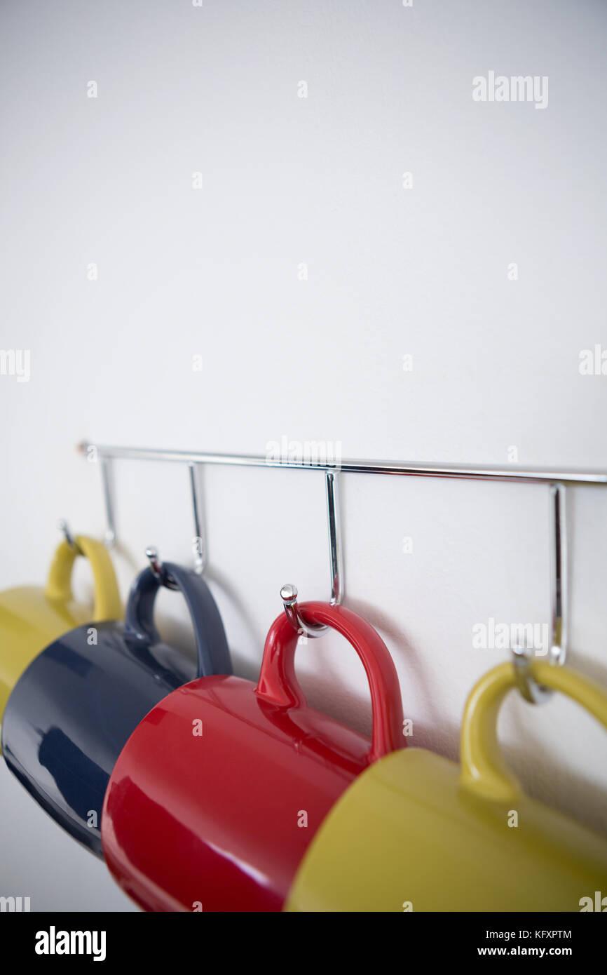 In Der Nähe Der Bunten Tassen Auf Haken Gegen Weiße Wand Hängen