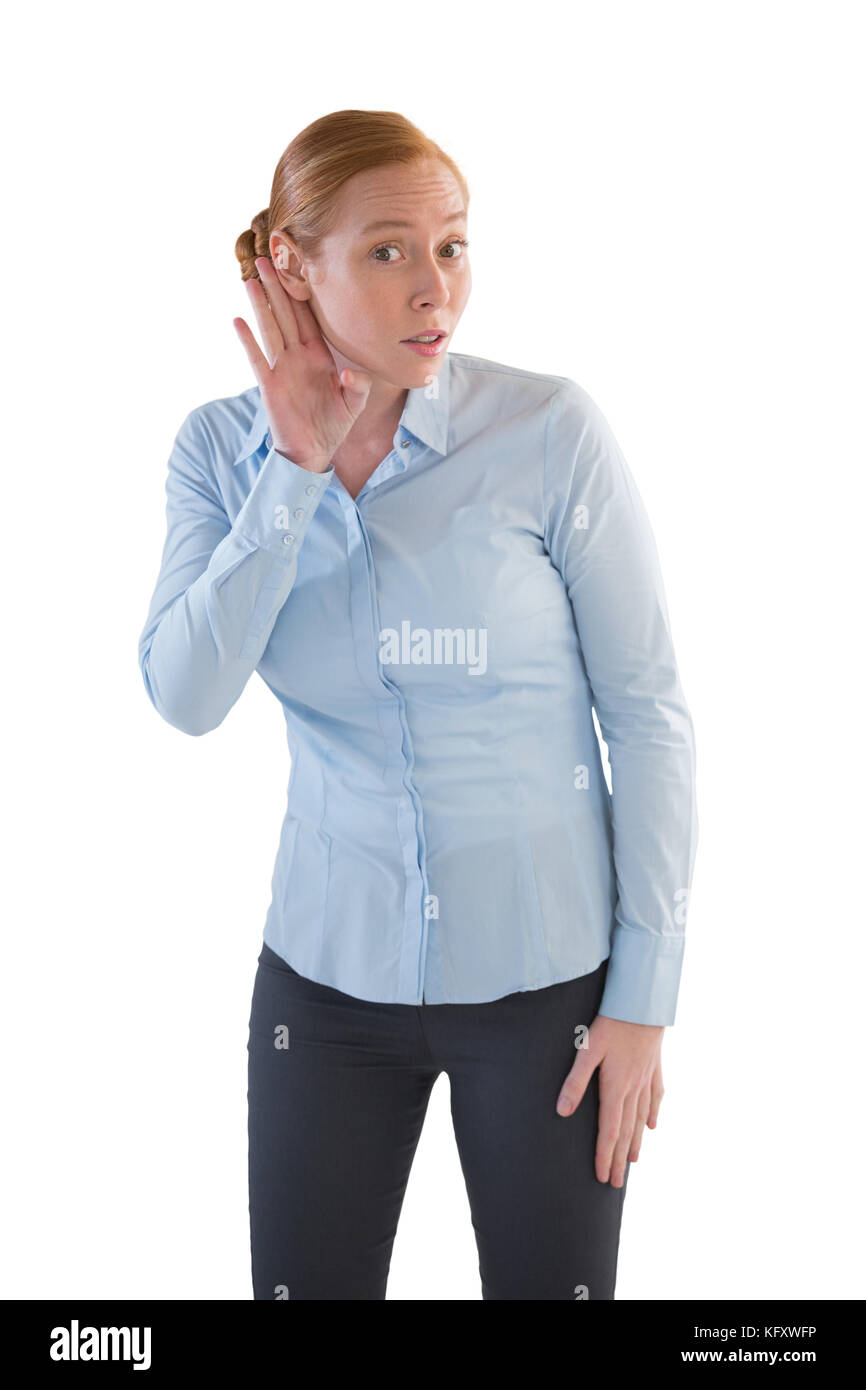 Junge weibliche Executive heimlich Hören mit Hände hinter ihre Ohren Stockbild