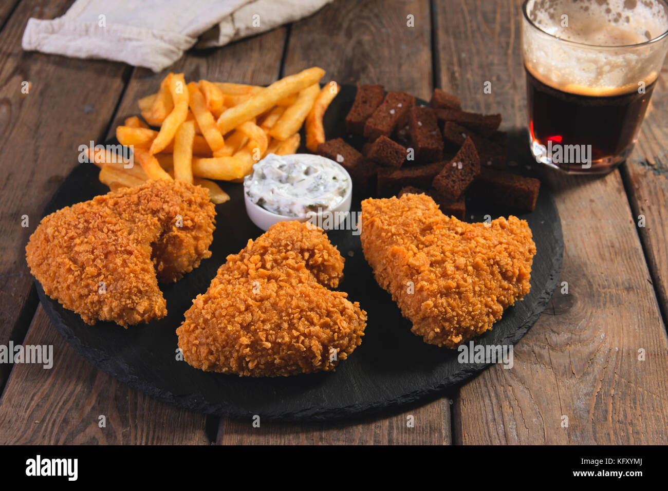 Fried Chicken Wings knusprig paniert mit Pommes frites frittiert Roggenbrot croutons Bier Snack Stockbild