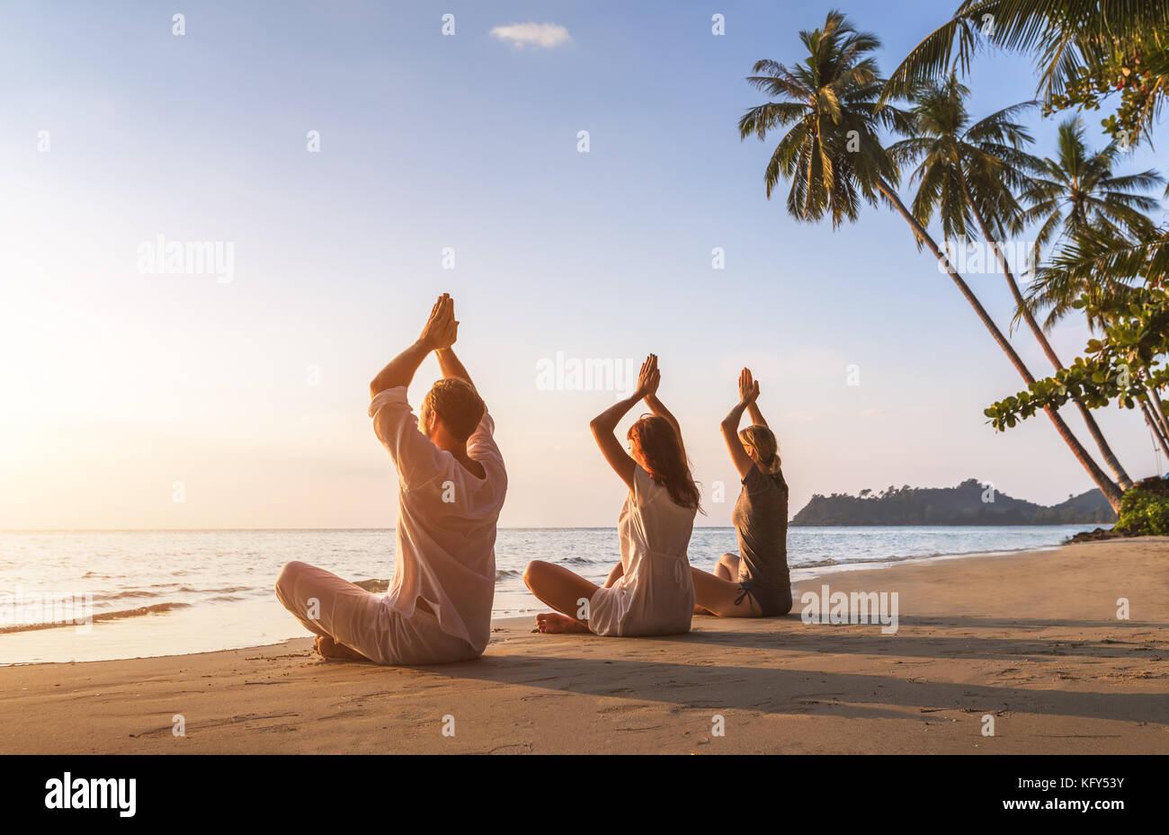 Eine Gruppe von drei Personen üben Yoga lotus Position am Strand für Entspannung und Wohlbefinden, warmen Stockbild