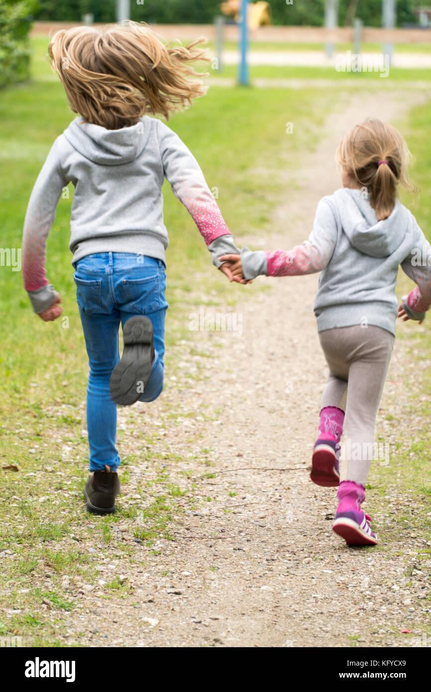 Zwei Mädchen laufen Hand in Hand über einen Sandweg Stockbild