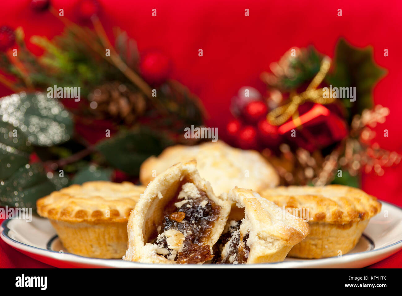 Nahaufnahme eines gebrochenen Mince Pie auf einer Platte mit einigen festlichen Weihnachtsschmuck auf rotem Hintergrund Stockbild