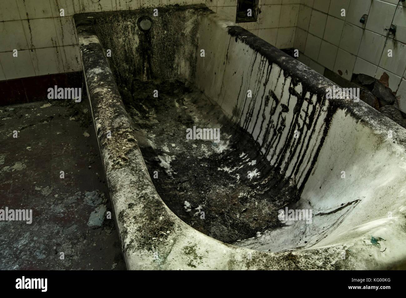 Eine alte Wanne in einem verlassenen psychiatrischen Krankenhaus, sehr Schmutz und verkrustete Stockbild