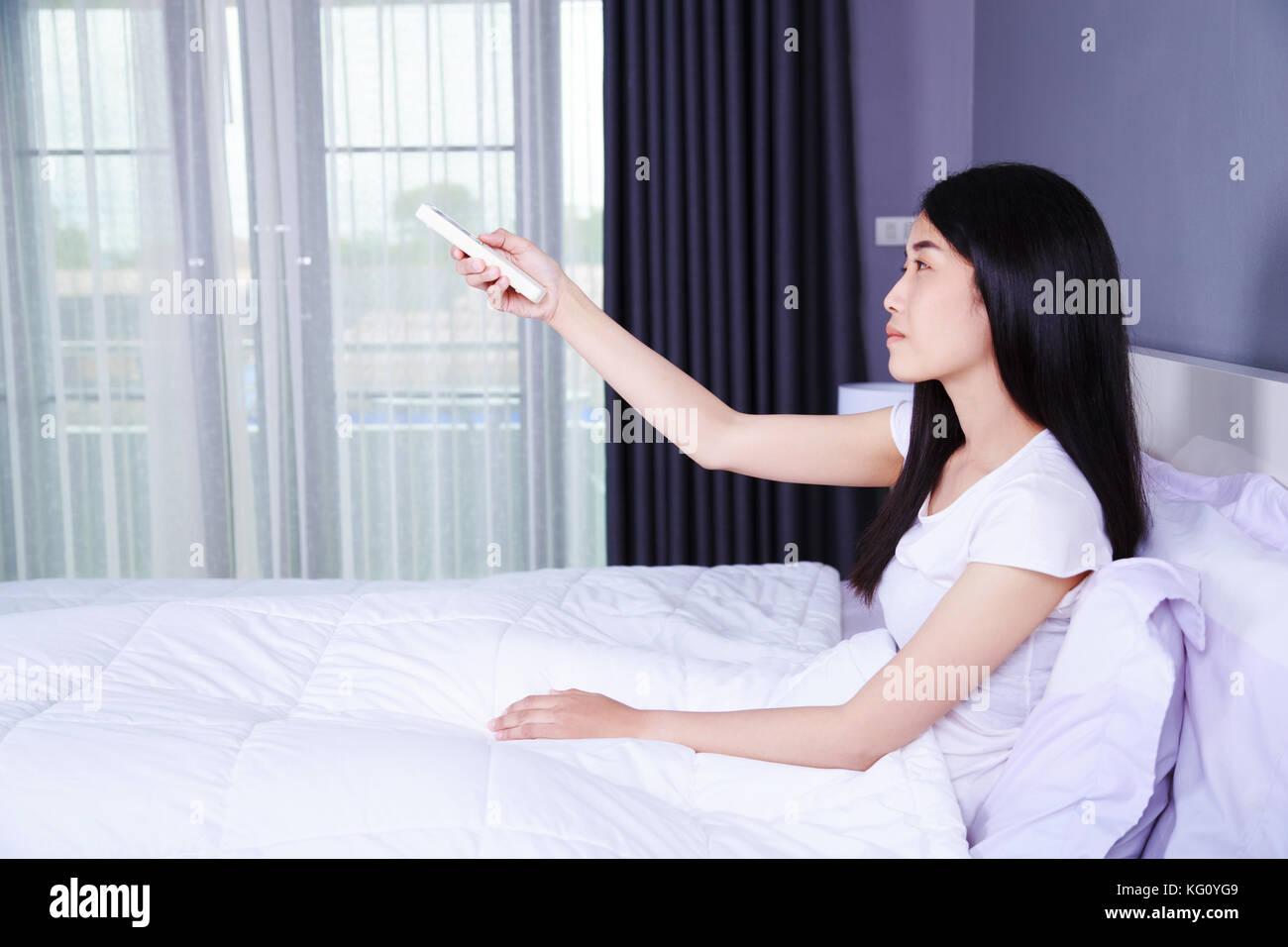 Frau Hand halten Fernbedienung Klimaanlage ein Bett im Schlafzimmer ...