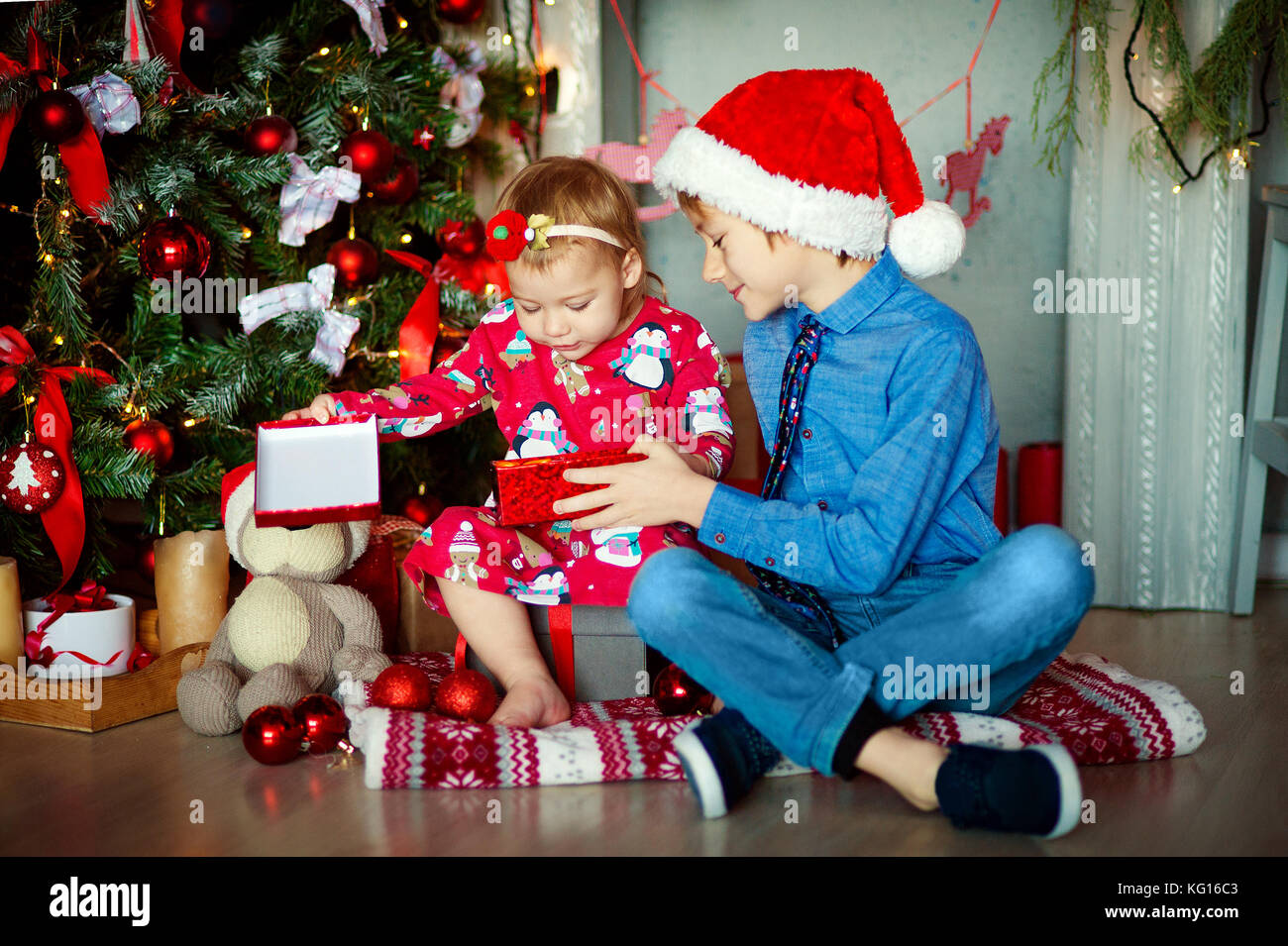 Familie am Weihnachtsabend am Kamin. Kinder Geschenke öffnen. Kinder ...