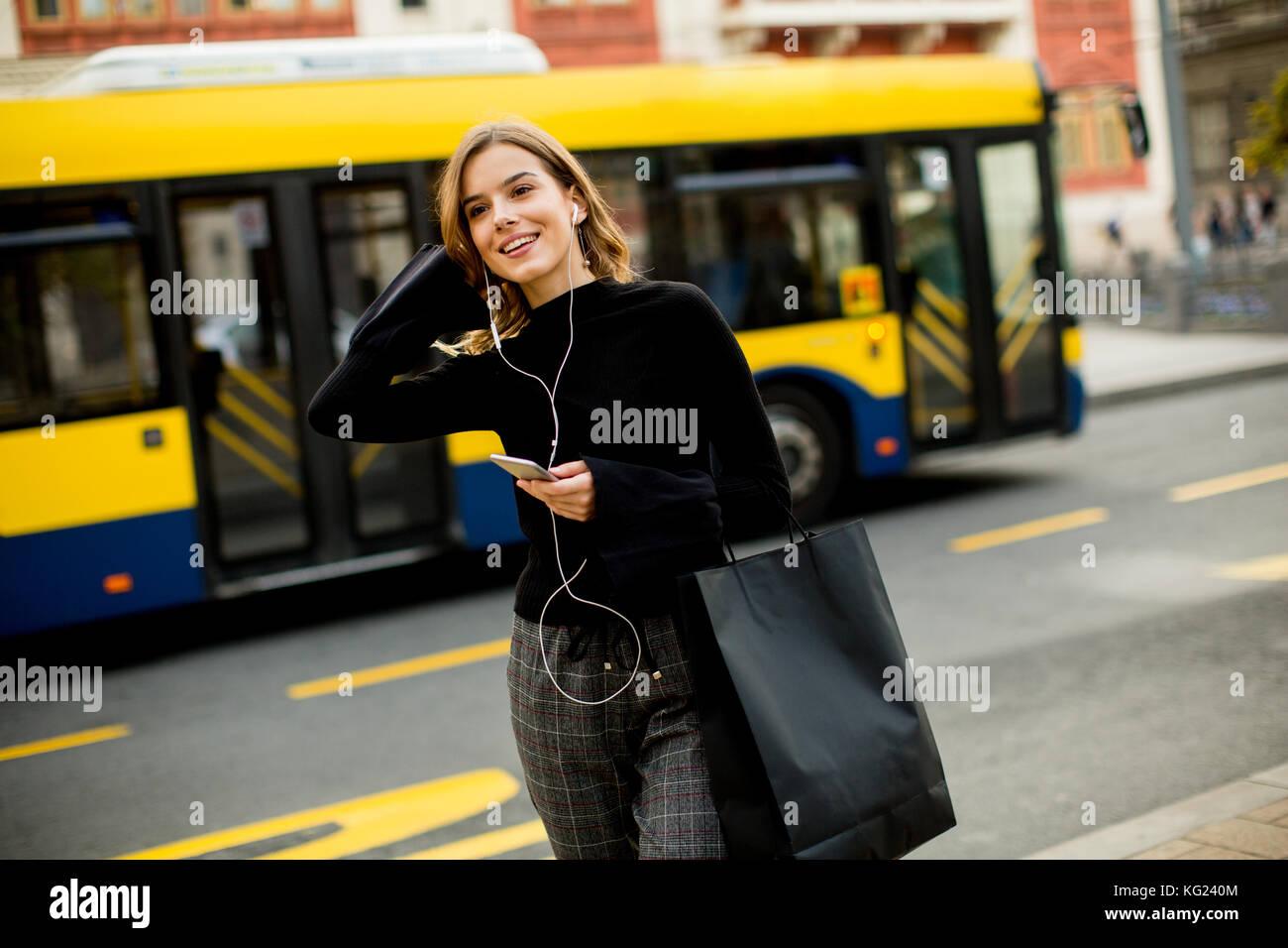 Junge Frau Warten auf dem Bus oder Taxi auf der Straße in der Stadt Stockfoto