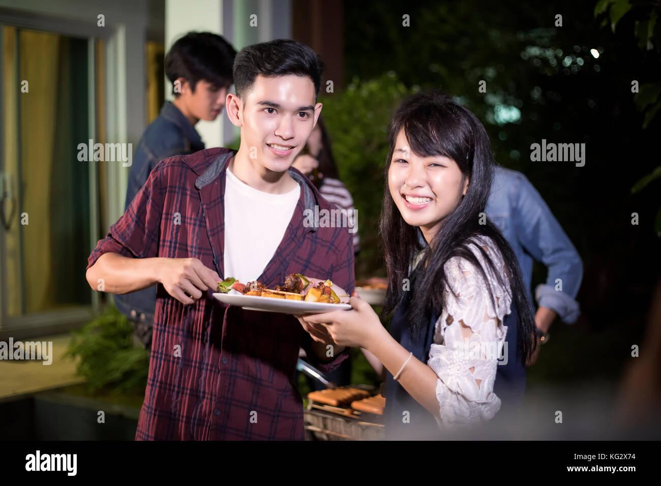Asiatisches junges Paar beim romantischen Dinner und eine Gruppe von Freunden in Außenbereich Garten Grill Stockbild