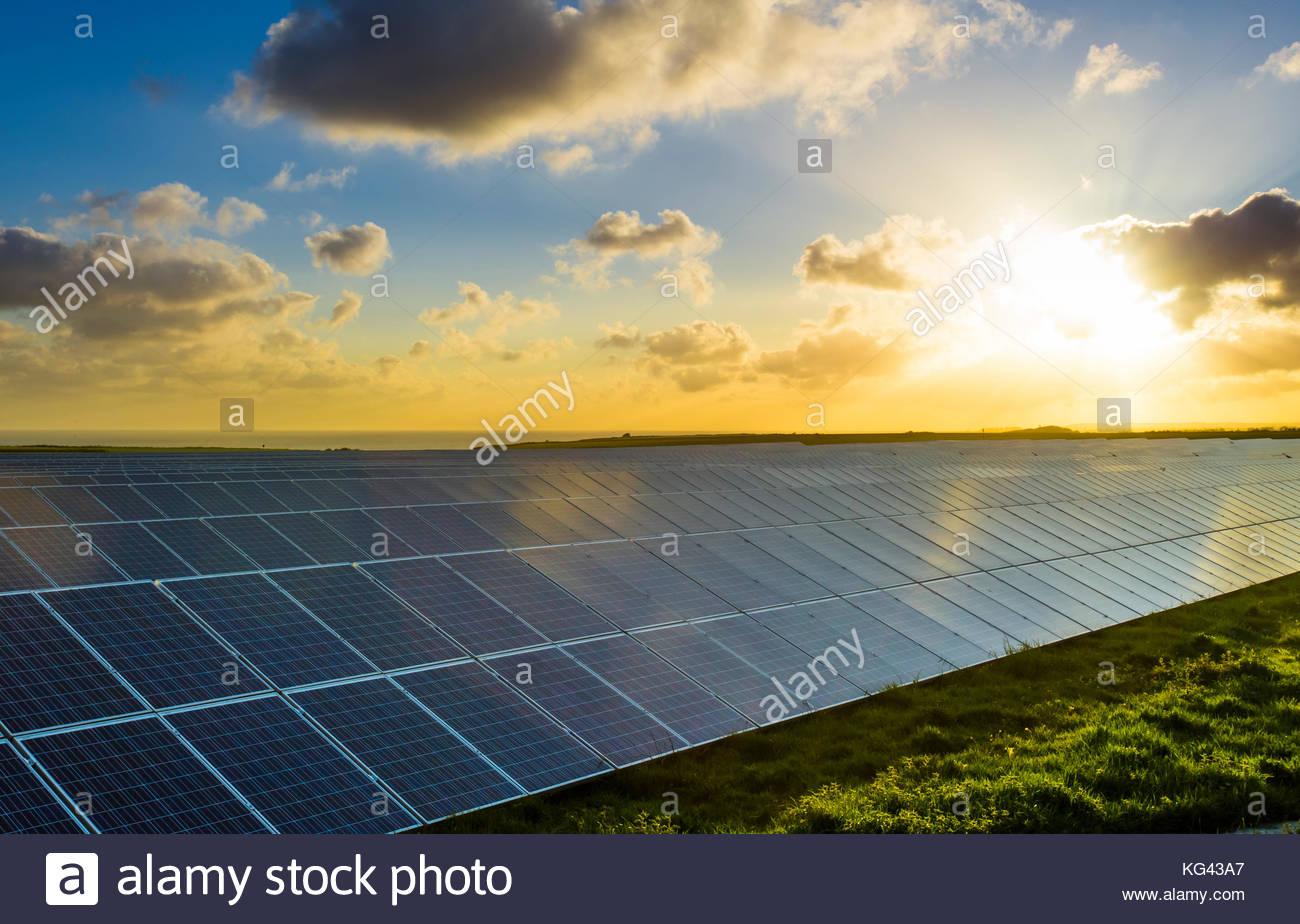 Sonnenkollektoren bei Sonnenaufgang mit bewölktem Himmel in der Normandie, Frankreich. Solarenergie, moderne Stockbild