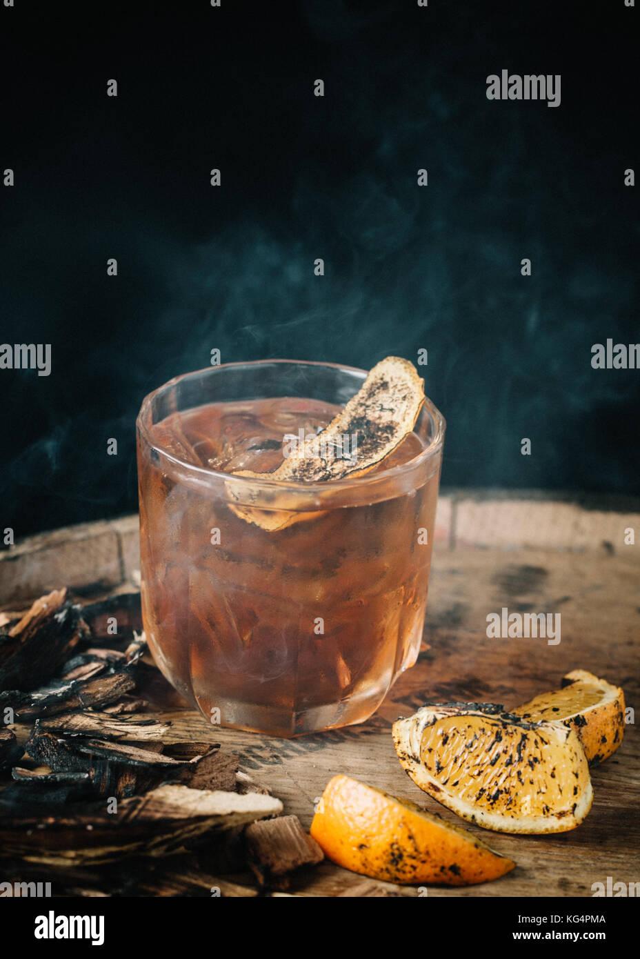 Geräucherter altmodische Cocktail garniert mit einer Orangenhaut auf dunklem Hintergrund Stockbild