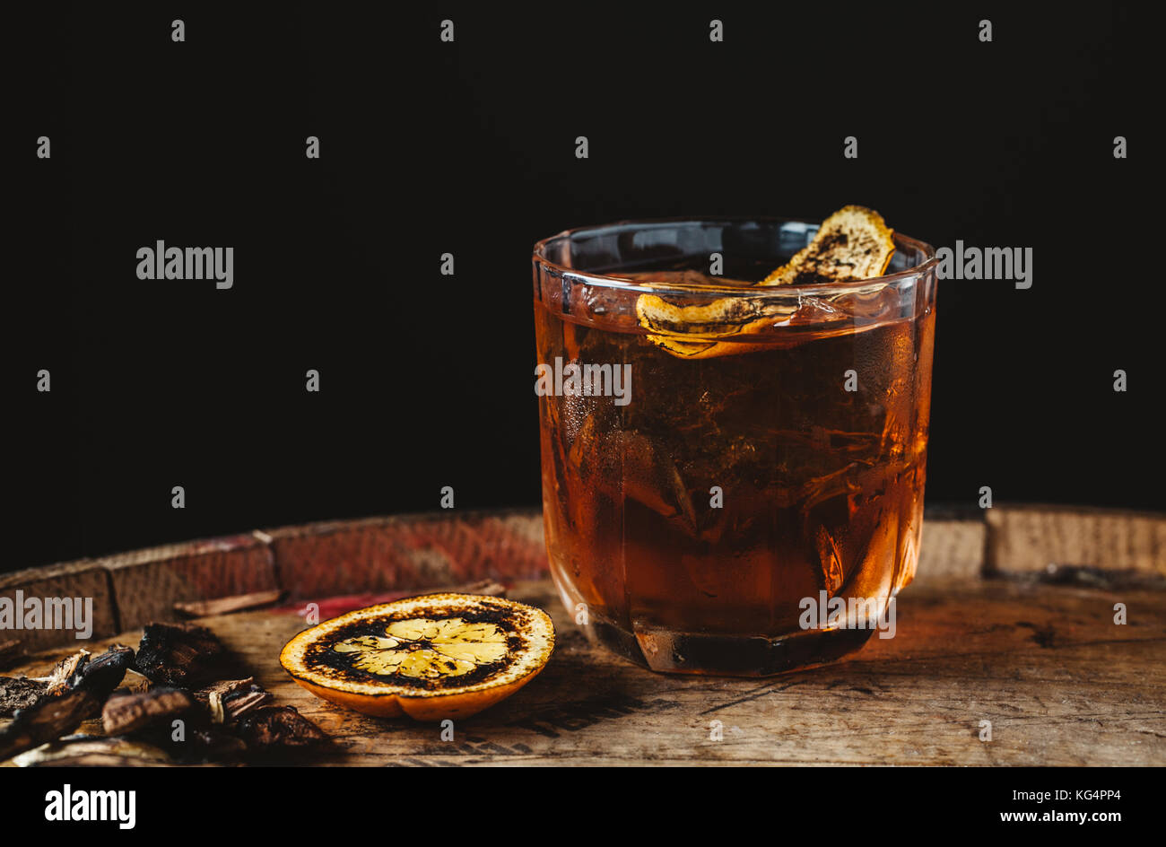 Geräucherter altmodische Cocktail garniert mit einer Orangenhaut auf dunklem Hintergrund Stockfoto