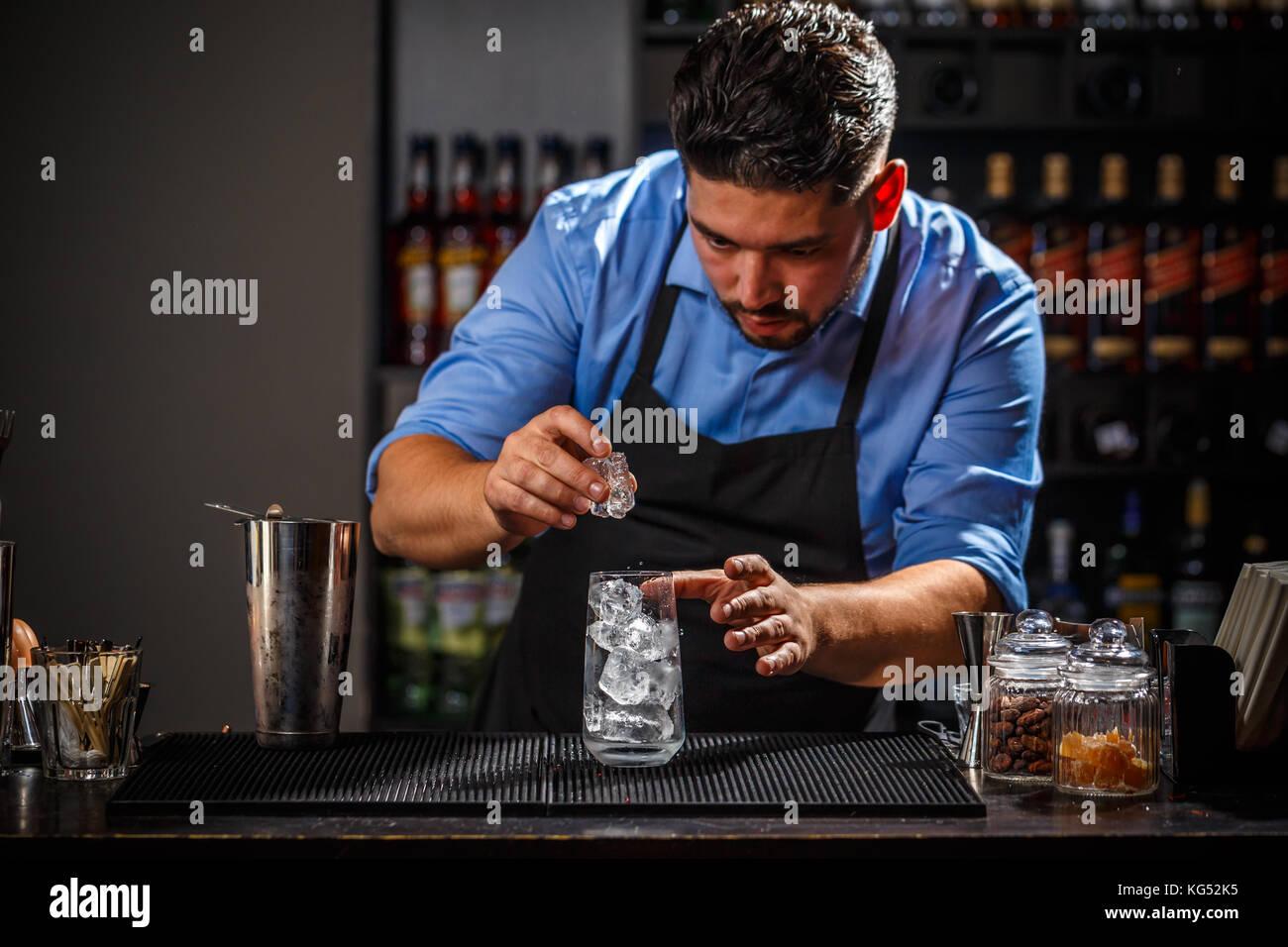 Barkeeper das Eis stellt Eiswürfel im Glas, Barkeeper arbeitet Stockbild