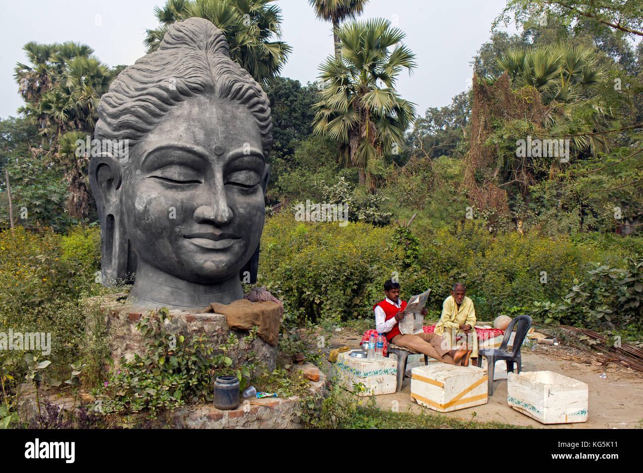 Zwei indische Männer ruhen in einem Hinterhof mit einem Hugh buddha Kopf mit Blick auf die Szene Stockbild