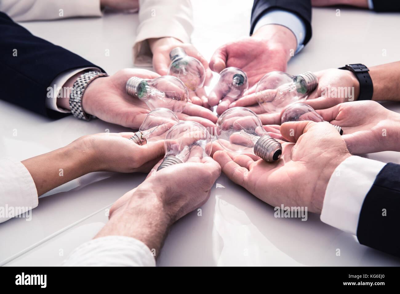 Teamarbeit und Brainstorming Konzept mit Geschäftsleuten, die eine Idee mit einer Lampe teilen. Konzept der Startup Stockfoto