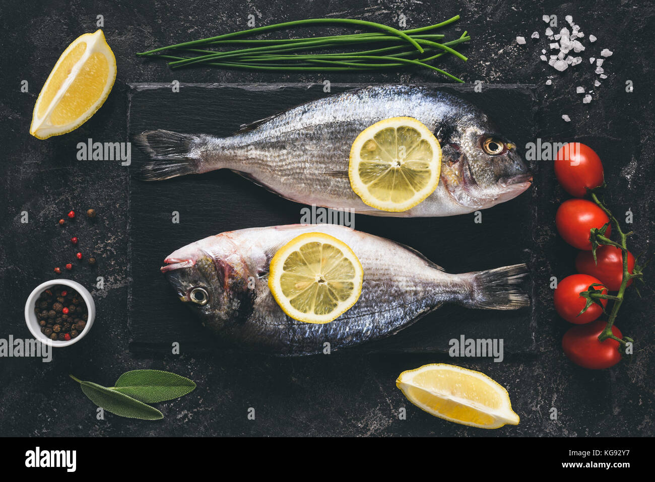 Frische Seeluft Strahl oder dorado Fisch-, Zitronen-, Kräuter, Gewürze und Gemüse auf schwarzen Stein Stockbild